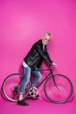 Veste en cuir de port à la mode heureuse d'homme supérieur, sunglesses et bicyclette de monte Photos libres de droits