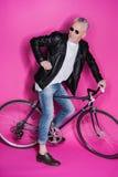 Veste en cuir de port élégante d'homme supérieur, sunglesses et bicyclette de monte Photo libre de droits