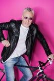Veste en cuir de port élégante d'homme supérieur, sunglesses et bicyclette de monte Photographie stock libre de droits