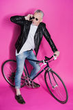 Veste en cuir de port élégante d'homme supérieur utilisant le smartphone et la bicyclette de monte Photographie stock libre de droits