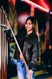 Veste en cuir de port de jeune belle fille dans un club de billard, avec le bâton de queue se préparant au jeu photo stock