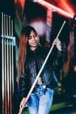 Veste en cuir de port de jeune belle fille dans un club de billard, avec le bâton de queue se préparant au jeu image stock