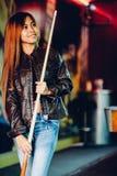 Veste en cuir de port de jeune belle fille dans un club de billard, avec le bâton de queue se préparant au jeu images stock