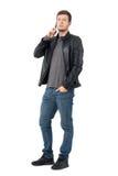 Veste en cuir de port de jeune homme occasionnel sûr au téléphone avec la main dans la poche Image libre de droits