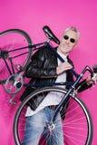 Veste en cuir de port gaie et sunglesses d'homme supérieur tenant la bicyclette sur ses épaules Photos stock