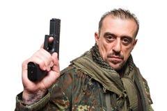 Veste masculine de militaires de terroriste revolver en sa main image stock