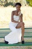 Vestido adolescente negro atractivo de la muchacha que se sienta al aire libre Imagen de archivo