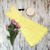 Vestido amarillo femenino en un fondo de madera imagen de archivo