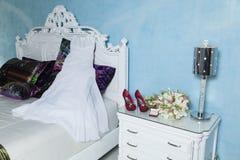 Vestido, anillos, zapatos y ramo para casarse Foto de archivo