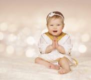 Vestido antigo do bebê, menina roupa branca nas mãos dobradas, uma da criança Fotografia de Stock