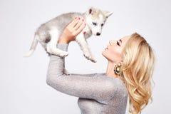 Vestido atractivo hermoso del maquillaje del perro de animales domésticos del abrazo de la mujer rubio Foto de archivo
