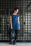 Vestido azul hermoso del lunar de la mujer que lleva joven que presenta por la cerca y que mira abajo Fotos de archivo