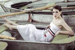 Vestido blanco del verano de la mujer que lleva atractiva que se sienta en b metálico Fotos de archivo libres de regalías
