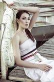 Vestido blanco del verano de la mujer que lleva hermosa que se sienta en la empanada de madera Fotos de archivo