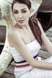 Vestido blanco del verano de la mujer que lleva hermosa que se sienta en la empanada de madera Fotografía de archivo libre de regalías
