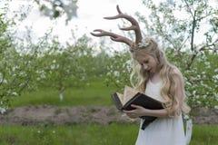 Vestido blanco que lleva de la muchacha rubia hermosa adolescente con los cuernos o de los ciervos Foto de archivo