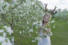 Vestido blanco que lleva de la muchacha rubia hermosa adolescente con los cuernos o de los ciervos Fotos de archivo libres de regalías