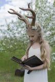 Vestido blanco que lleva de la muchacha rubia hermosa adolescente con los cuernos o de los ciervos Fotografía de archivo