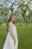 Vestido blanco que lleva de la muchacha rubia hermosa adolescente con los cuernos o de los ciervos Foto de archivo libre de regalías