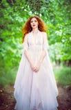 Vestido blanco que lleva de la mujer pelirroja linda en un jardín imagenes de archivo