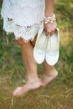 Vestido bonito branco vestindo da moça descalça que guarda sapatas foto de stock