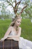 Vestido branco vestindo da menina loura adolescente com os chifres dos cervos em sua cabeça Fotografia de Stock Royalty Free