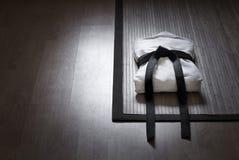 Vestido da arte marcial no tapete de bambu Foto de Stock Royalty Free