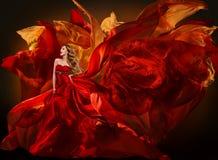 Vestido da forma da mulher que voa a tela vermelha, pano de seda de ondulação da menina Foto de Stock Royalty Free