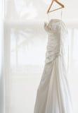 Vestido de boda blanco que se sostiene cerca de la ventana Imagen de archivo libre de regalías