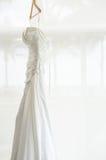 Vestido de boda blanco que se sostiene en el cuarto Fotografía de archivo