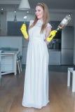 Vestido de boda de la mujer que lleva que sostiene la cacerola en cocina imagen de archivo libre de regalías