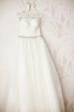 Vestido de boda elegante magnífico en la suspensión en la pared Imágenes de archivo libres de regalías