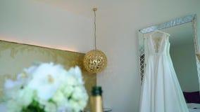 Vestido de boda en un espejo en dormitorio en el hotel de lujo Ramo nupcial de las rosas blancas almacen de metraje de vídeo