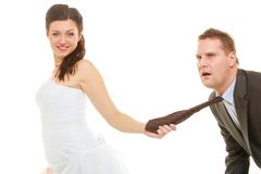 Vestido de boda de la novia que lleva dominante que tira del lazo del novio fotos de archivo