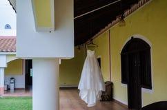 Vestido de boda que cuelga sobre el pasillo de un interior del hotel, barras de madera en el tejado de un pasillo del hotel imagen de archivo libre de regalías