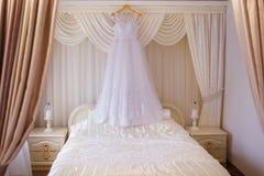 Vestido de casamento bonito que pendura na sala do ` s da noiva Foto de Stock