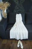 Vestido de casamento branco que encontra-se em um sofá cinzento Sapatas brancas nupciais foto de stock