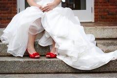 Vestido de casamento branco vestindo da noiva e sapatas vermelhas Foto de Stock