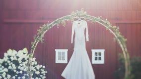 Vestido de casamento elegante que pendura do arco decorado com as flores na luz do dia vídeos de arquivo