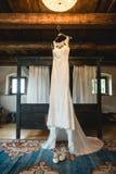 Vestido de casamento que pendura em uma sala de hotel rustical Imagens de Stock