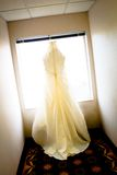 Vestido de casamento que pendura na janela Fotografia de Stock Royalty Free