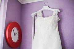Vestido de casamento que pendura no vermelho da parede e do relógio Imagens de Stock Royalty Free