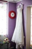 Vestido de casamento que pendura no vermelho da parede e do relógio Imagem de Stock Royalty Free