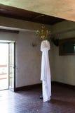 Vestido de casamento rústico que pendura no candelabro na sala fotos de stock