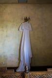 Vestido de casamento rústico que pendura no candelabro na sala imagens de stock royalty free
