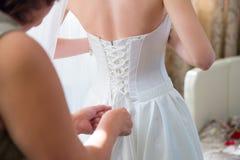 Vestido de casamento vestindo da noiva Imagem de Stock