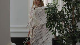 Vestido de jogo bonito da mulher elegante perto das colunas da construção filme