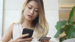 Vestido de la compra de la mujer nuevo en línea usando tarjeta del smartphone y de crédito almacen de video