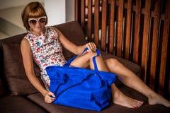 Vestido de la flor de la mujer joven del encanto que lleva que presenta con el bolso hecho a mano de lujo del pitón del snakeskin Imagenes de archivo