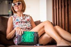 Vestido de la flor de la mujer joven del encanto que lleva que presenta con el bolso hecho a mano de lujo del pitón del snakeskin Fotografía de archivo libre de regalías